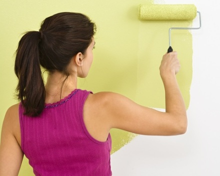 Woman painting a wall with paint roller_shutterstock_6694768