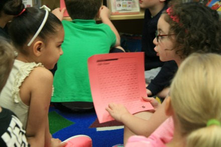 First grade math partners using the hundreds chart (photo taken with parent permission)